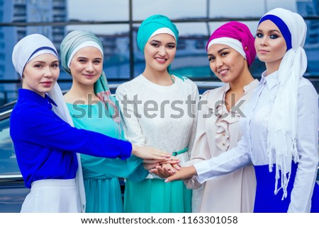 a group of five young and attractive business women in Muslim dress multi-colored hijab and a turban covering the head working thumbs up stacking hands puts palm together on the centre team work #1163301058
