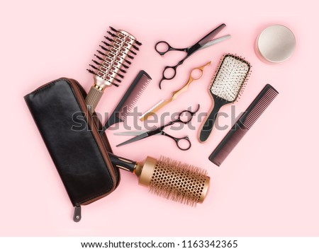 Hair dresser tool set with leather bag on pink background #1163342365