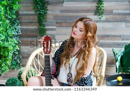A beautiful girl with red curly hair sits on a chair with a seven-string guitar. Hippie girl in the Studio. #1163346349