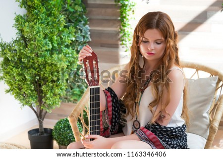 A beautiful girl with red curly hair sits on a chair with a seven-string guitar. Hippie girl in the Studio. #1163346406