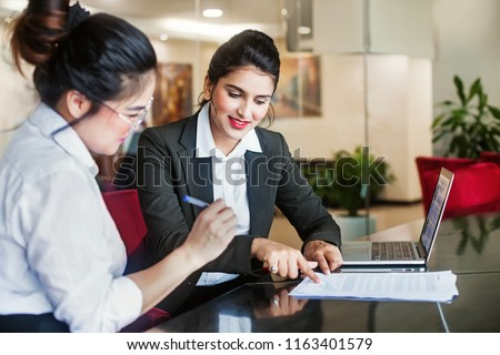 Indian female agent helping client sign the application document #1163401579
