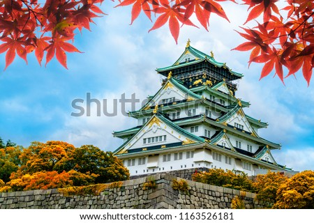 Osaka Castle in Osaka,Kansai,Japan in Fall or Autumn season. Maple tree are turn into red and orange leaf. There are red leaf in foreground.It is one of most famous landmark in Japan #1163526181