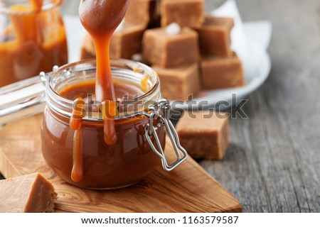 Homemade salted caramel sauce in jar on rustic wooden table. #1163579587
