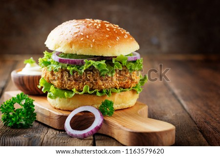 Fresh tasty chicken burger on wood table. #1163579620