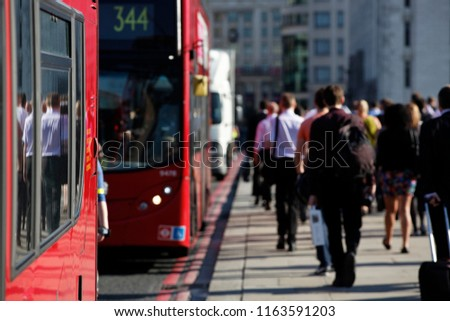 Pedestrian commuters in London walking to work alongside red buses travelling in opposite direction. #1163591203