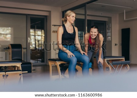 Women sitting on a bench in gym relaxing while her trainer is laughing. Women doing pilates workout at the gym. #1163600986