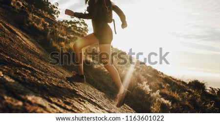 Woman running up a rocky mountain slope. Cropped shot of female trail runner running uphill on a sunny day. #1163601022