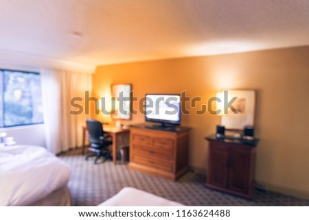 Motion blurred typical double room with windows, flat-screen TVs in American hotel #1163624488