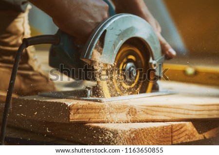 Close-up of a carpenter using a circular saw to cut a large board of wood #1163650855