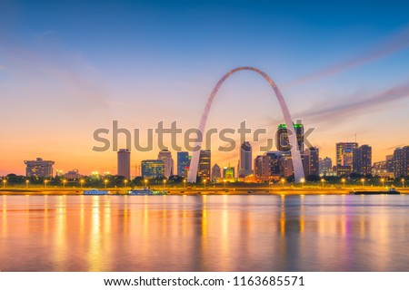 St. Louis, Missouri, USA downtown cityscape with the arch on the Mississippi River at dusk.