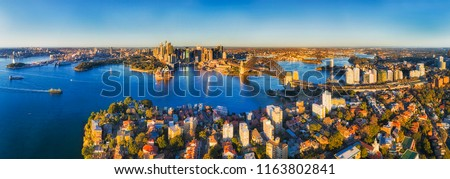 Sydney harbour shores in view of city CBD landmarks and the Harbour bridge connecting to North shore with Kirribilli residential suburb around Warringah freeway. #1163802841