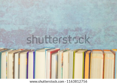 Books onbookshelf, blue background, vintage toned. Education, knowledge, reading, back to school theme. #1163812756