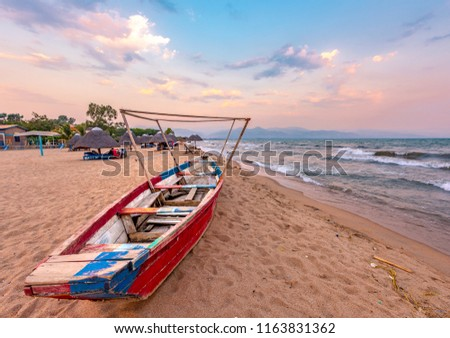 Burundi Bujumbura lake Tanganyika, windy cloudy sky and sand beach at sea lake in East Africa, Burundi sunset with boat from wood. Thatch african roofs on umbrellas #1163831362