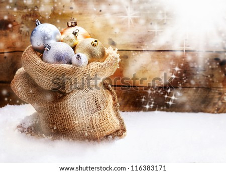 Hessian sack filled to overflowing with gold and silver Christmas baubles resting on snow in front of a rustic wooden wall with twinkling snowflakes and copyspace