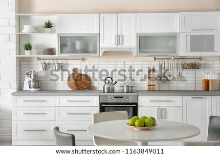 Stylish kitchen interior with dining table and chairs #1163849011