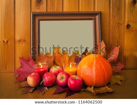 Apples, candles, pumpkin and picture frame on wooden table