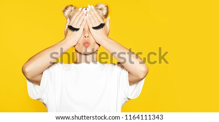Portrait of girl with blond hair sending air kiss with fake eyelash on hands on yellow background. Concept of emotions.  #1164111343