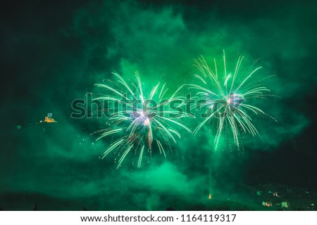 Wonderful couple of green fireworks on the feast of the patron saint of the city whose church is visible in the background, Vittorio Veneto, Italy