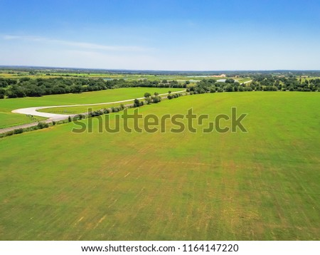 Aerial view green farmland and rolling hill landscape with scenic drive in Hill Country, West Texas, USA. Horizontal shot countryside and ranch flyover, blue sky