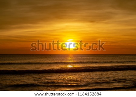 A vibrant and beautiful sunset at Karon Beach Thailand. Combinations of deep oranges, reds and yellows combine with light yellows/  The clouds look fluffy and the view is looking out into the ocean. #1164152884