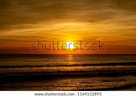 A vibrant and beautiful sunset at Karon Beach Thailand. Combinations of deep oranges, reds and yellows combine with light yellows/  The clouds look fluffy and the view is looking out into the ocean. #1164152893