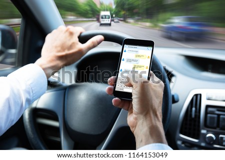 Close-up Of A Man's Hand Typing Text Message On Mobile Phone While Driving Car #1164153049