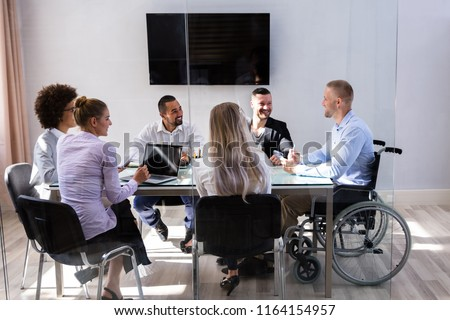 Disabled Male Manager Sitting With His Colleagues At Workplace Royalty-Free Stock Photo #1164154957