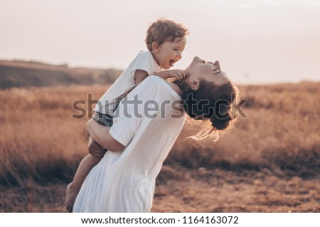 Young woman kisses her little son at sunny in the meadow in sunset. Young mother holding her baby. Mother and  little son having good time in the nature. Color toned image. Mothers Day. Family Concept #1164163072