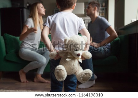 Rear view at kid boy holding toy while parents fighting, little son suffering from parents arguments, lack of attention or divorce, bad family relationships and psychological impact on child concept #1164198310