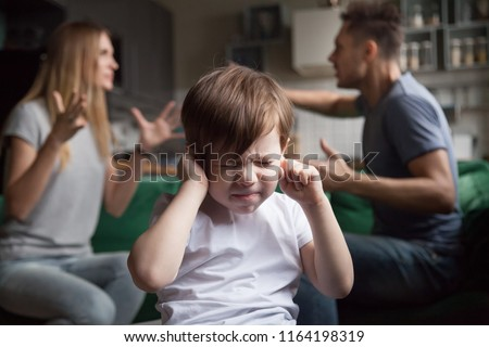 Frustrated kid son puts fingers in ears not listening to noisy parents arguing, stressed preschool boy suffering from mom and dad fighting shouting, family conflicts negative impact on child concept Royalty-Free Stock Photo #1164198319
