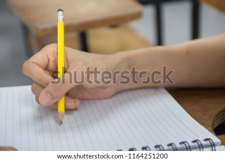 hand high school or university student in uniform holding pencil writing on paper answer sheet.sitting on lecture chair taking final exam or study attending in examination room or classroom #1164251200