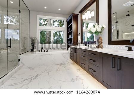 Master modern bathroom interior in luxury home with dark hardwood cabinets, white tub and glass door shower #1164260074