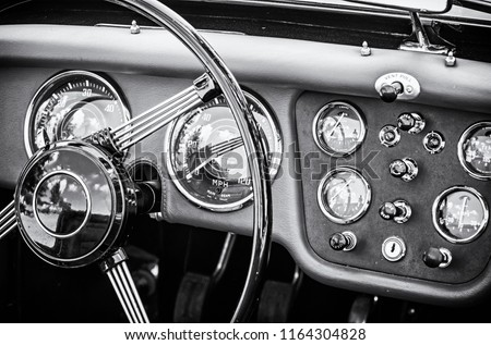 Steering wheel and dashboard in historic vintage red car. Retro automobile interior scene. Old vehicle. Driving theme. Black and white photo. #1164304828