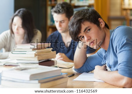 Student leaning on table looking tired at the library #116432569