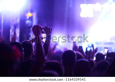 Use advanced mobile recording, fun concerts and beautiful lighting, Candid image of crowd at rock concert, Close up of recording video with smartphone, Enjoy the use of mobile photography. #1164339541