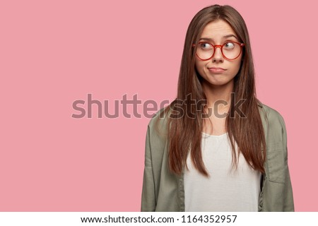 Horizontal portrait of thoughtful puzzled youngster looks with pensive dreamy expression aside, thinks what decision to make, stands against pink background with blank copy space on left side #1164352957