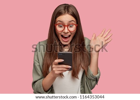 Overjoyed happy excited female glad to recieve text message informing about salary, rejoices good news, stares at mobile phone, gestures actively from happiness, stands indoor alone. Reaction concept #1164353044