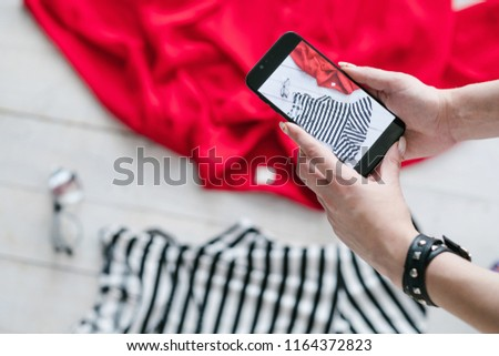 still life mobile photography. hobby and creative lifestyle concept. woman taking photos of clothing on smartphone.