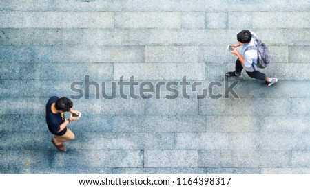 Aerial top view with blur man with smartphone walking converse with busy city crowd move to pedestrian crosswalk #1164398317
