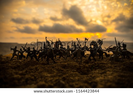 Medieval battle scene with cavalry and infantry. Silhouettes of figures as separate objects, fight between warriors on sunset foggy background. Selective focus #1164423844