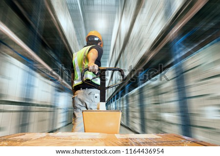 Storehouse area, Shipment. Speeding motion of warehouse worker unloading pallet goods in warehouse storage, his using with hand pallet truck.  #1164436954