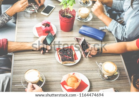 Top view of young friends drinking coffee in bar restaurant - People hands doing breakfast inside cafeteria - Job break, food and lifestyle concept - Main focus on tattoed girl hand #1164474694