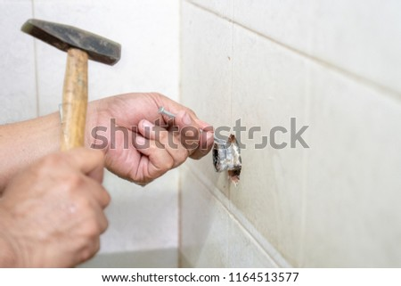 Asian man tries to fix and repair pipe / shower in the old restroom. #1164513577