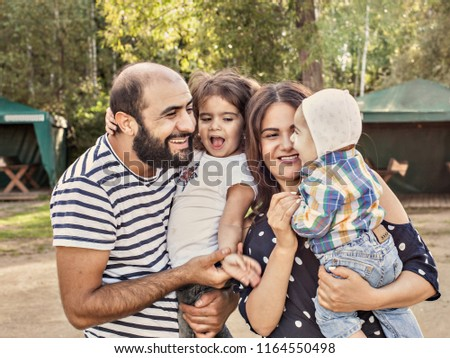 photo of a happy family . Mom dad newborn and four year old girl spend time in the Park in summer. #1164550498