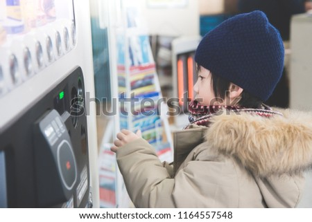 Cute Asian child purchasing soft drink from vending machine in the train station #1164557548