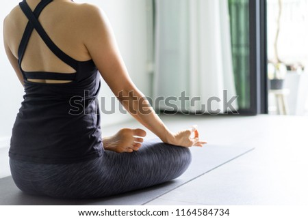 Young woman practicing yoga in  gray background.Young people do yoga indoor.Close up hands in meditating gesture. Copy space. #1164584734