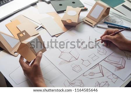 Designer sketching drawing design Brown craft cardboard paper product eco packaging mockup box development template package branding Label . designer studio concept . #1164585646