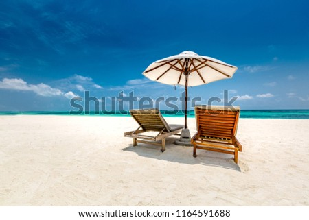 Seascape with two chaise longues, without people. Beautiful beach ocean vacation destination scene. Amazing Maldives island. Beach scene with copy space for text. Luxury summer holiday concept #1164591688