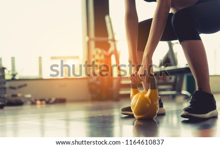 Woman exercise workout at gym fitness training sport with kettlebell weight lifting and legs squat healthy lifestyle bodybuilding. #1164610837