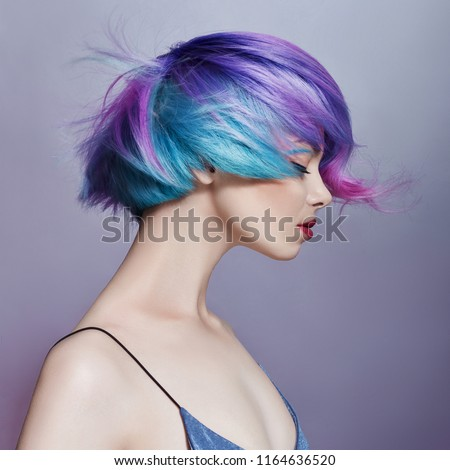 Portrait of a woman with bright colored flying hair, all shades of purple. Hair coloring, beautiful lips and makeup. Hair fluttering in the wind. Sexy girl with short hair #1164636520